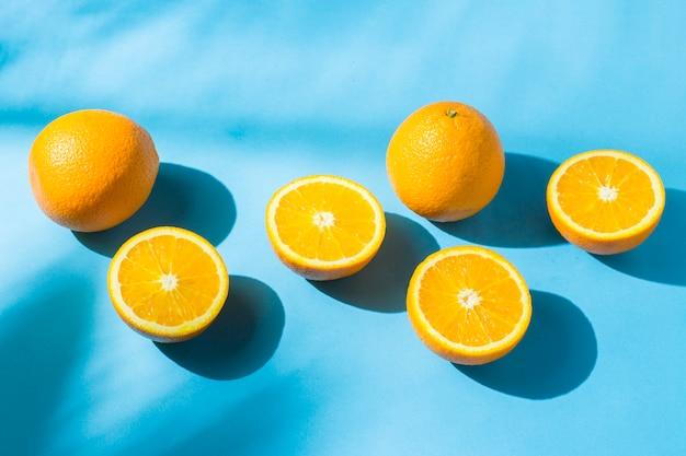 Sinaasappelen op een blauw oppervlak onder natuurlijk licht met schaduwen. hard licht. concept van voeding, gezond eten, rust in de tropen, vakantie en reizen, vitaminen.