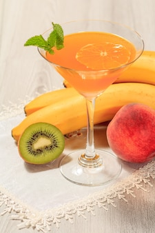 Sinaasappelgelei in de met glas bedekte muntblaadjes, nectarine, kiwi en banaan op het witte servet