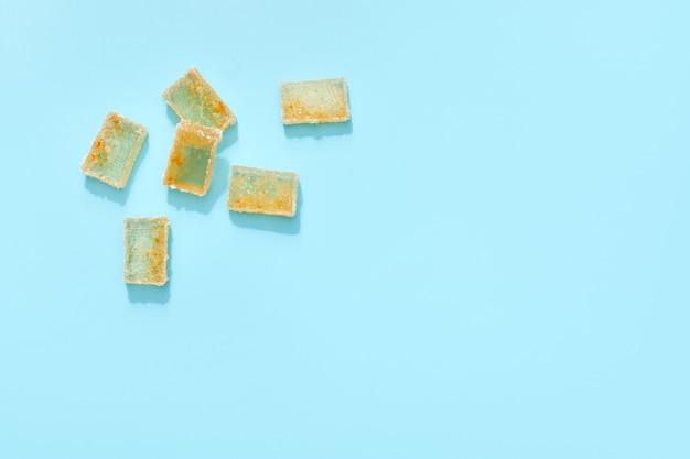 Sinaasappelgeleiplakken in suiker op blauwe achtergrond. citrusmarmelade. bovenaanzicht