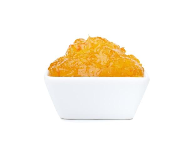 Sinaasappelmarmeladejam die op witte achtergrond wordt geïsoleerd