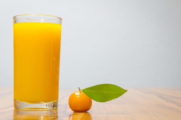 Sinaasappelsap en verwijderbare imitatie vruchten op houten tafel. kijk chup thailand.