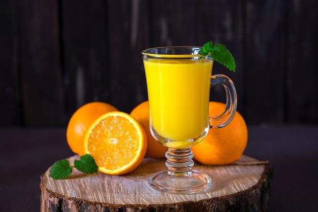 Sinaasappelsap in een glazen mok op een houten stomp