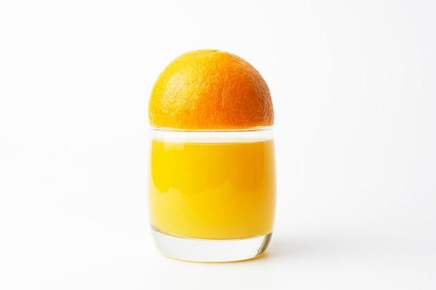 Sinaasappelsap in een helder glazen beker met verse sinaasappelen.
