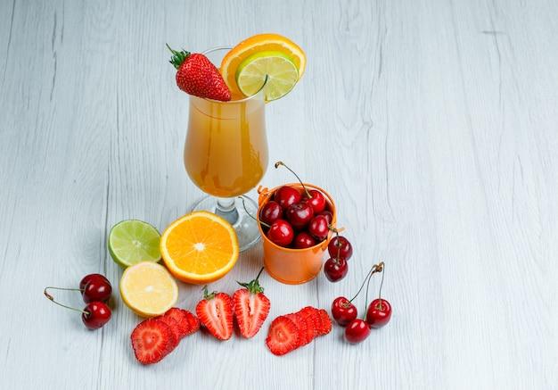 Sinaasappelsap met citroen, limoen, sinaasappel, aardbei, kers in een beker op houten oppervlak, hoge hoek bekijken.