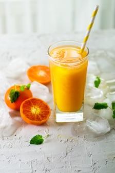 Sinaasappelsap met ijs en mandarijnen. copyspace. koude drank voor hete de zomerdag