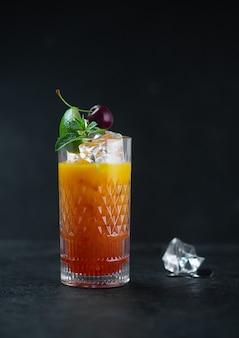 Sinaasappelsap met ijsmunt en kersen in een glas