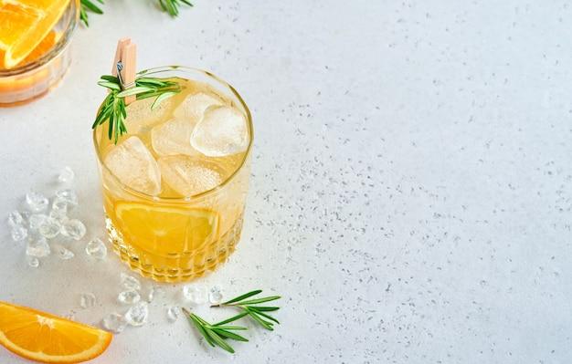 Sinaasappelsap of cocktail met rozemarijn en sinaasappel met ijs in glas, koude zomerlimonade op lichtgrijze leisteen, steen of betonnen ondergrond. strandconcept met diepe zonschaduw. bovenaanzicht.