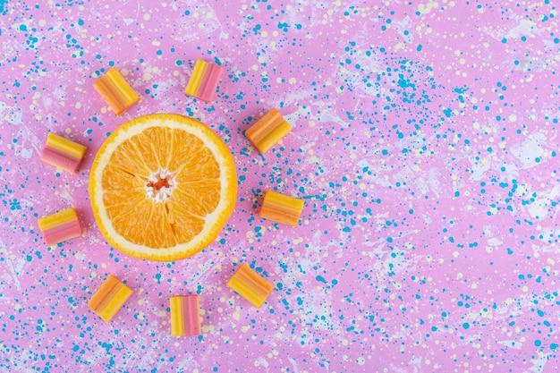 Sinaasappelschijfje en kauwgom gerangschikt in een som-motief op een kleurrijk oppervlak