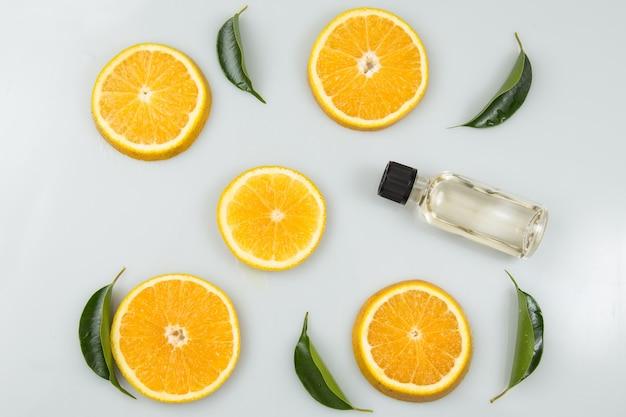 Sinaasappelschijfjes met bladeren en een fles