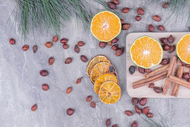 Sinaasappelschijfjes met droge heupen en kaneel op een grijze schaal