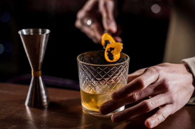 Sinaasappelschil in alcoholcocktail bij toog. barman maakt jungle juice-cocktail in bar