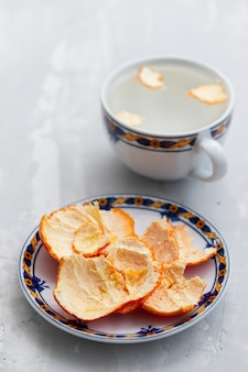 Sinaasappelschil op plaat en in een kop met heet water
