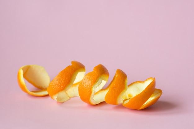 Sinaasappelschil op roze achtergrond als een symbool van recycling circuleert economie
