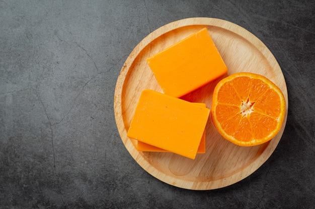 Sinaasappelzeep met verse sinaasappel op donkere achtergrond