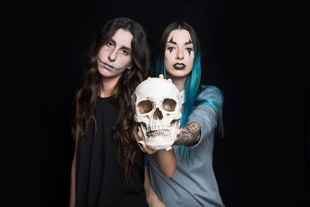 Sinistere meisjes die schedel houden