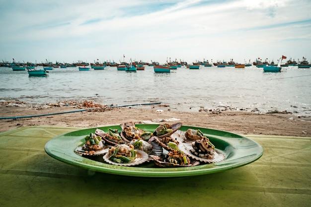 Sint-jakobsschelpen op een bord tegen de kust met ronde vietnamese boten. restaurant aan het strand. aziatisch zeevruchten eten. traditionele vietnamese keuken.