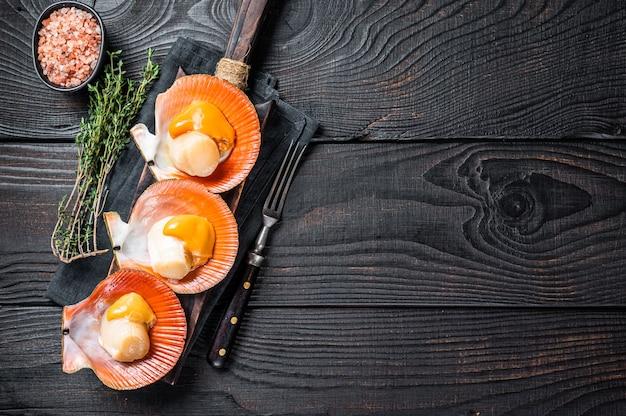 Sint-jakobsschelpen rauwe schelpdieren op een houten bord met kruiden. zwarte houten achtergrond. bovenaanzicht. ruimte kopiëren.