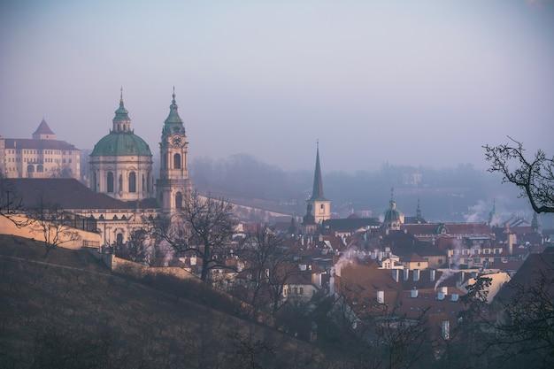 Sint-nicolaaskathedraal en de stad van praag in de ochtendmist