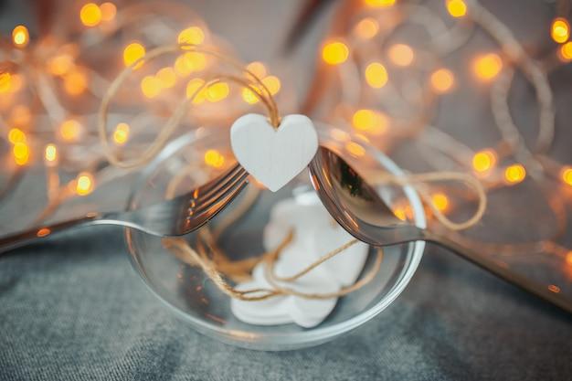 Sint-valentijnsdag kaart. witte houten harten op de lichte achtergrond. harten met slingerlichten. lepel en vork houden een hart vast met heldere bokeh.