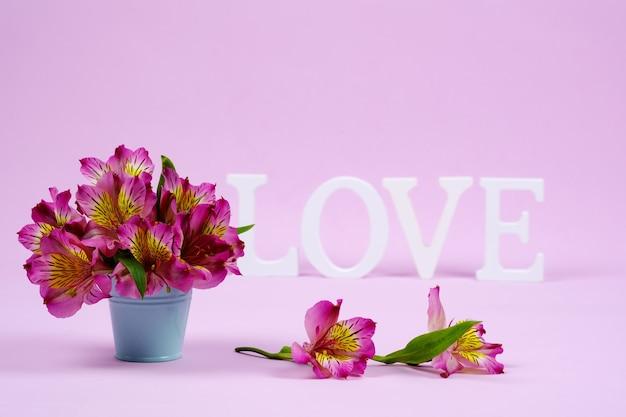 Sint-valentijnskaart. paarse alstroemeria's op de voorgrond en het woord liefde in de muur. kopieer ruimte voor uw tekst, roze muur