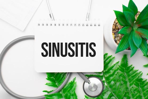 Sinusitiswoord op notitieboekje, stethoscoop en groene plant