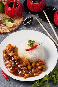 Sissende kung pao-kip met geroosterde pinda's op een witte plaat