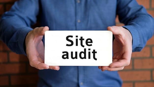 Site-audit - seo-concept in handen van een jonge man in een blauw shirt