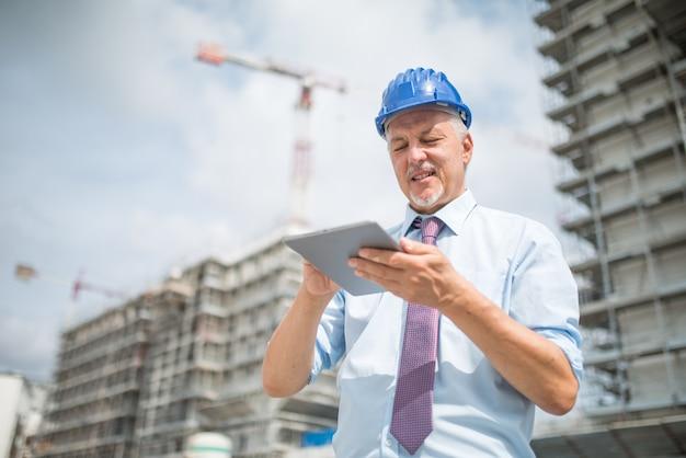 Sitebeheerder die zijn tablet voor een bouwwerf gebruikt