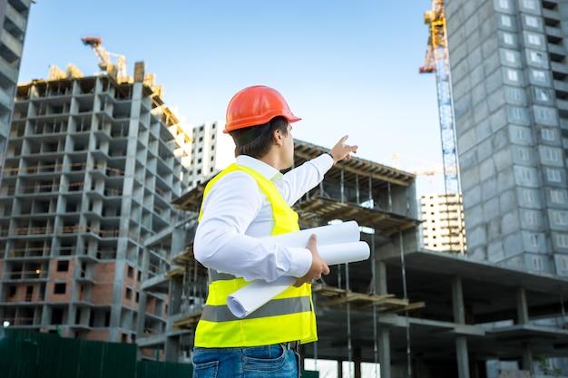 Sitemanager in veiligheidshelm wijzend op kraan op bouwplaats