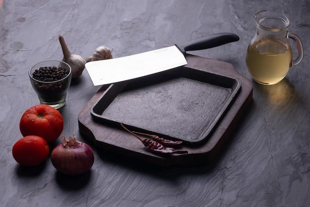 Sizzler met mes en kookingrediënten gerangschikt op een grijze gestructureerde achtergrond