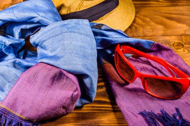 Sjaal, strohoed en bril op rustieke houten tafel