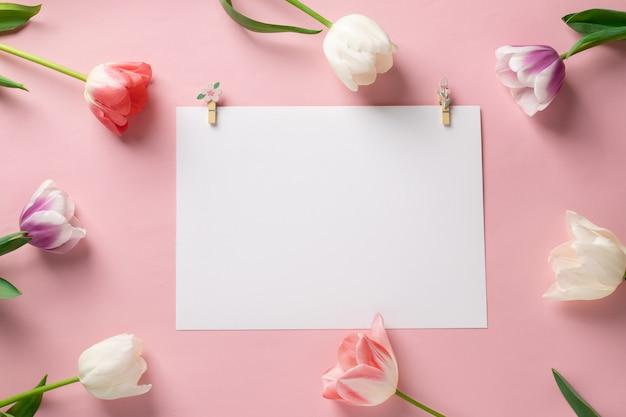 Sjabloon met blanco wit papier met kleurrijke bloemen op een roze achtergrond. ansichtkaart met tulpen voor elk evenement met ruimte voor tekst.