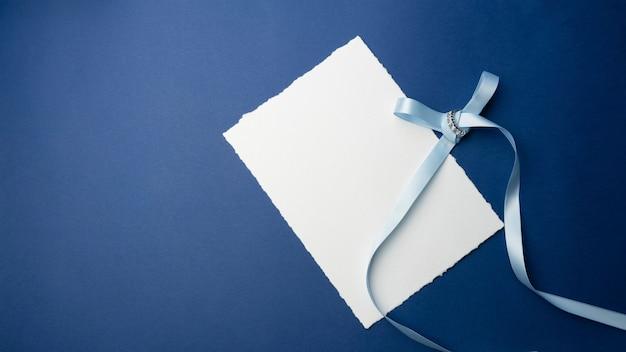 Sjabloon voor uitnodigingen, groeten. op een blauwe achtergrond een wit vel papier, een envelop, een notitieboekje, een ring met stenen en decoratieve kaarsen. minimalistisch ontwerp voor bruiloft, verjaardag.