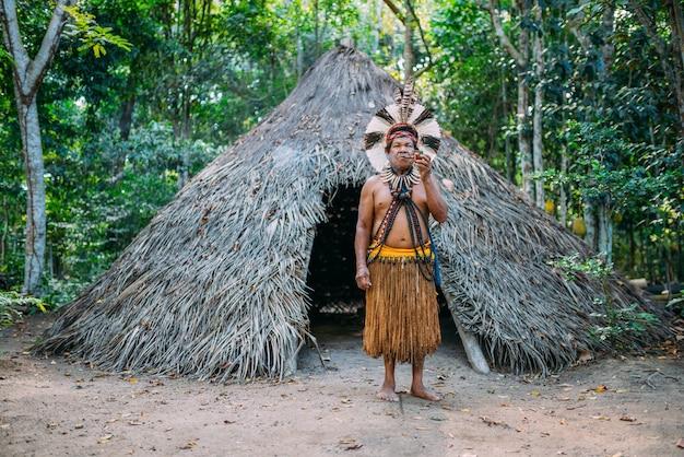 Sjamaan van de pataxã³-stam, met een hoofdtooi van veren en rookt een pijp