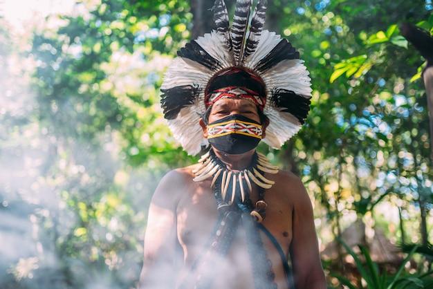 Sjamaan van de pataxã³-stam. oudere indiase man met een hoofdtooi van veren en een gezichtsmasker vanwege de covid-19 pandemie