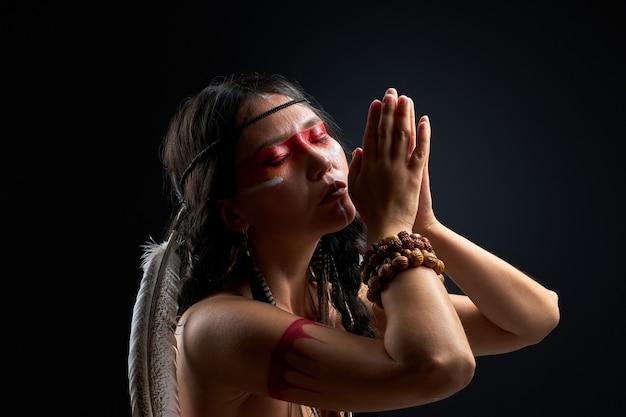 Sjamanistisch vrouwtje met indiase veer op haar en kleurrijk geschilderde make-up Premium Foto