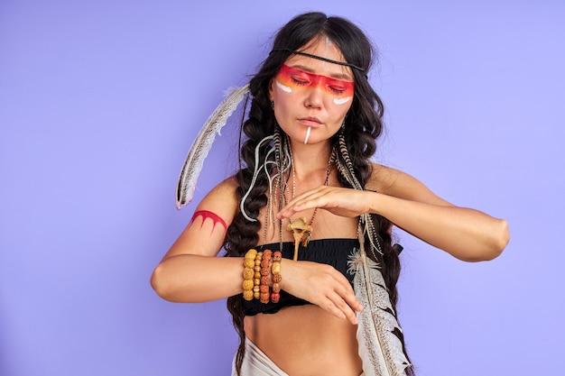 Sjamanistisch vrouwtje met indiase veer op haar en kleurrijk geschilderde make-up