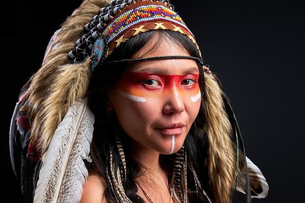 Sjamanistische vrouw met krijger sjamaan make-up geïsoleerd in studio, kleurrijke schilderijen op haar gezicht en lichaam, ze is