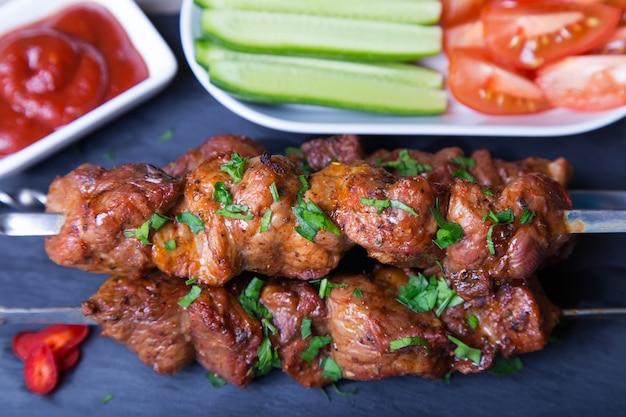 Sjasliek (shish kebab) van vlees (varkensvlees) op spiesjes met groenten en ketchup. close-up, selectieve aandacht.