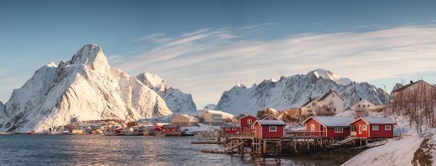 Skandinavisch dorp met sneeuwberg bij kustlijn in ochtend