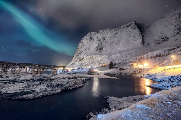 Skandinavische dorpsverlichting met noordelijke lichten die op sneeuwberg glanzen