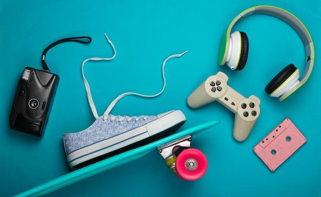 Skateboard en sneaker, koptelefoon en andere accessoires op blauwe ondergrond