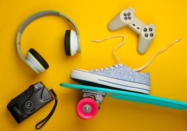 Skateboard en sneaker, koptelefoon en andere accessoires op geel oppervlak