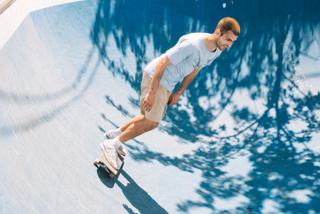Skateboarder die en op helling glimlacht berijdt