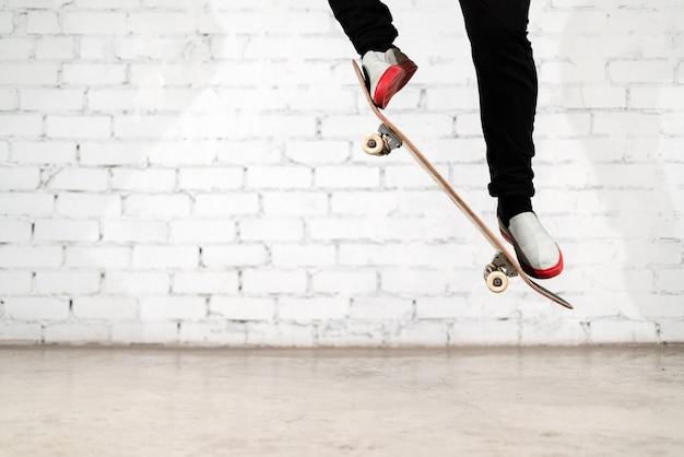 Skateboarder die skateboardtruc uitvoert - ollie op beton.