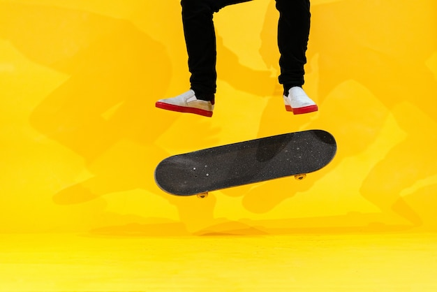 Skateboarder die skateboardtruc uitvoert - schop flip in de studio.