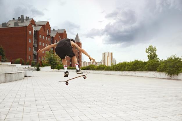 Skateboarder doet een truc in de straat van de stad op een bewolkte dag