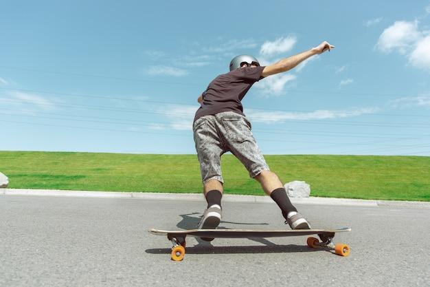 Skateboarder doet een truc in de straat van de stad op zonnige dag. jonge man in uitrusting rijden en longboarden in de buurt van weide in actie. concept van vrijetijdsbesteding, sport, extreem, hobby en beweging.