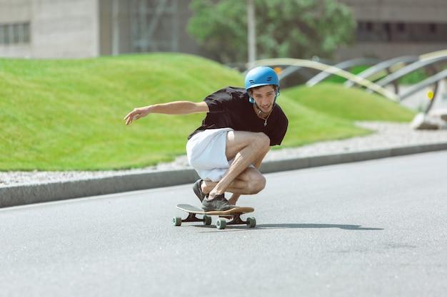 Skateboarder doet een truc in de straat van de stad op zonnige dag. jonge man in uitrusting rijden en longboarden op het asfalt in actie. concept van vrijetijdsbesteding, sport, extreem, hobby en beweging.