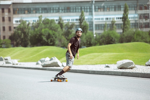 Skateboarder doet een truc in de straat van de stad op zonnige dag